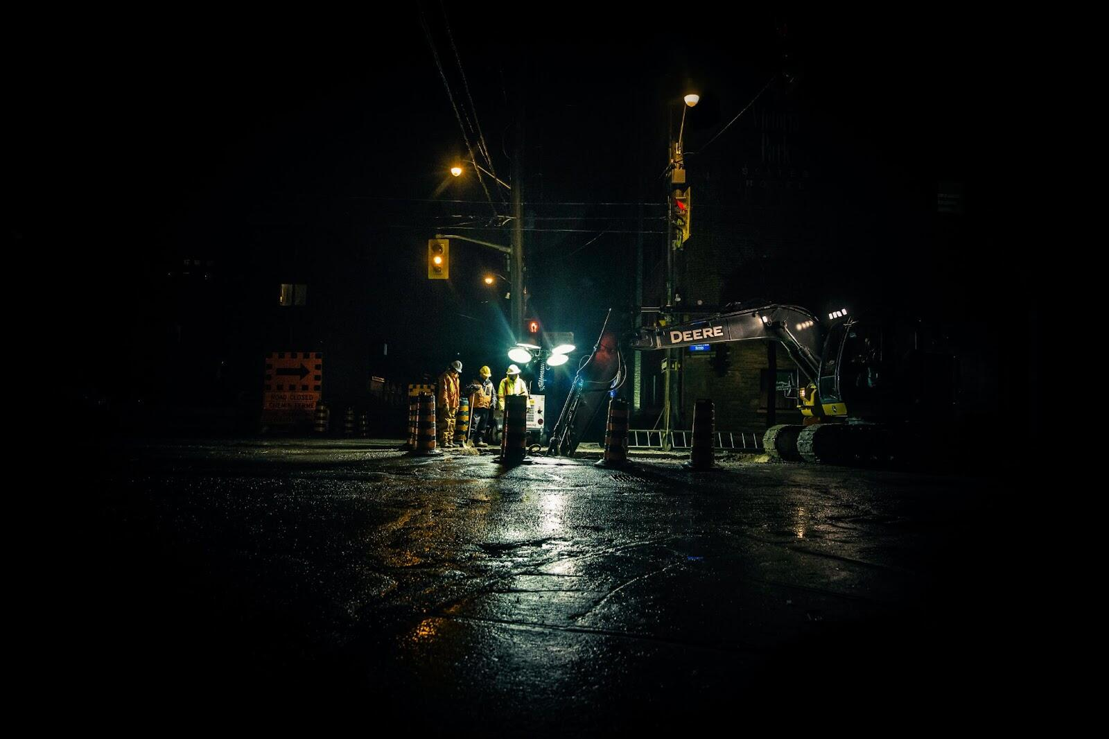 A road work zone at night with workers surrounded by traffic control supplies