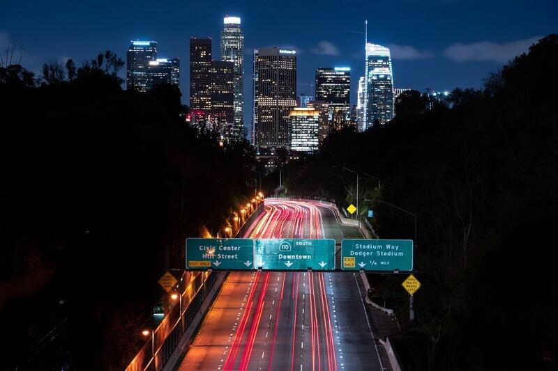A freeway at night with road safety signs above the roads