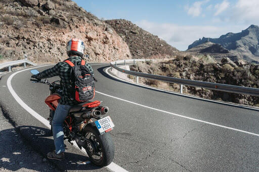 A motorcyclist pulled over on the side of a mountain highway