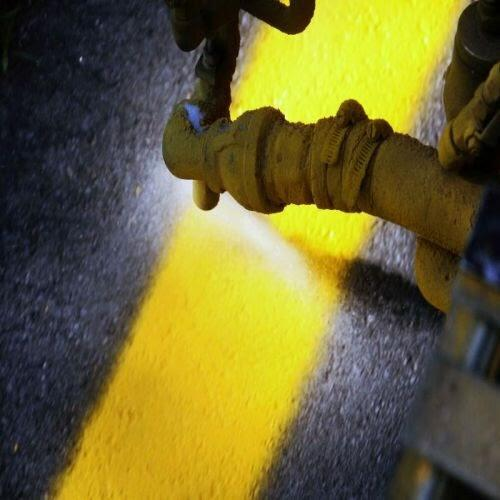 A tool spraying yellow, reflective paint onto the asphalt