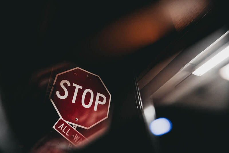 A Stop sign that is obscured and not easily visible