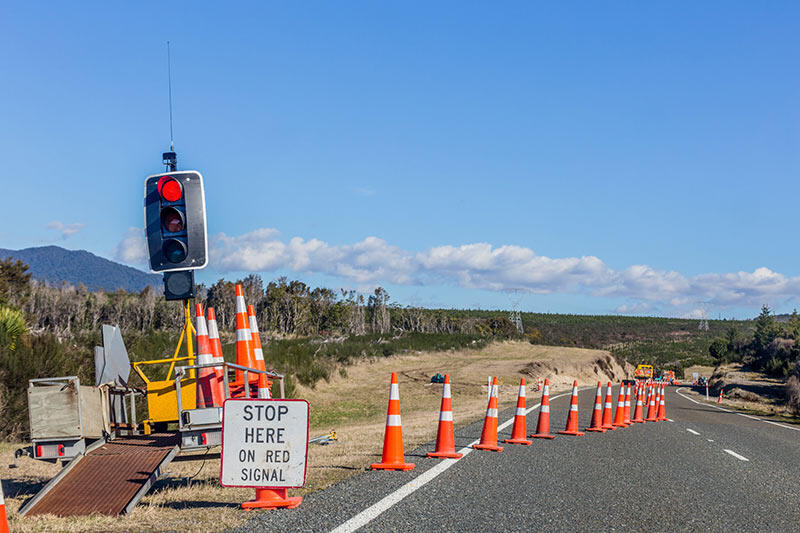 A construction site set up with orange cones, a stoplight, and other construction traffic signs to help inform drivers