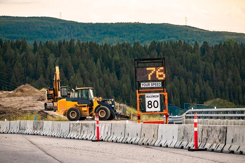 A construction zone set up on a highway with highway barricades, a traffic speed sign, and other construction safety products near the mountains