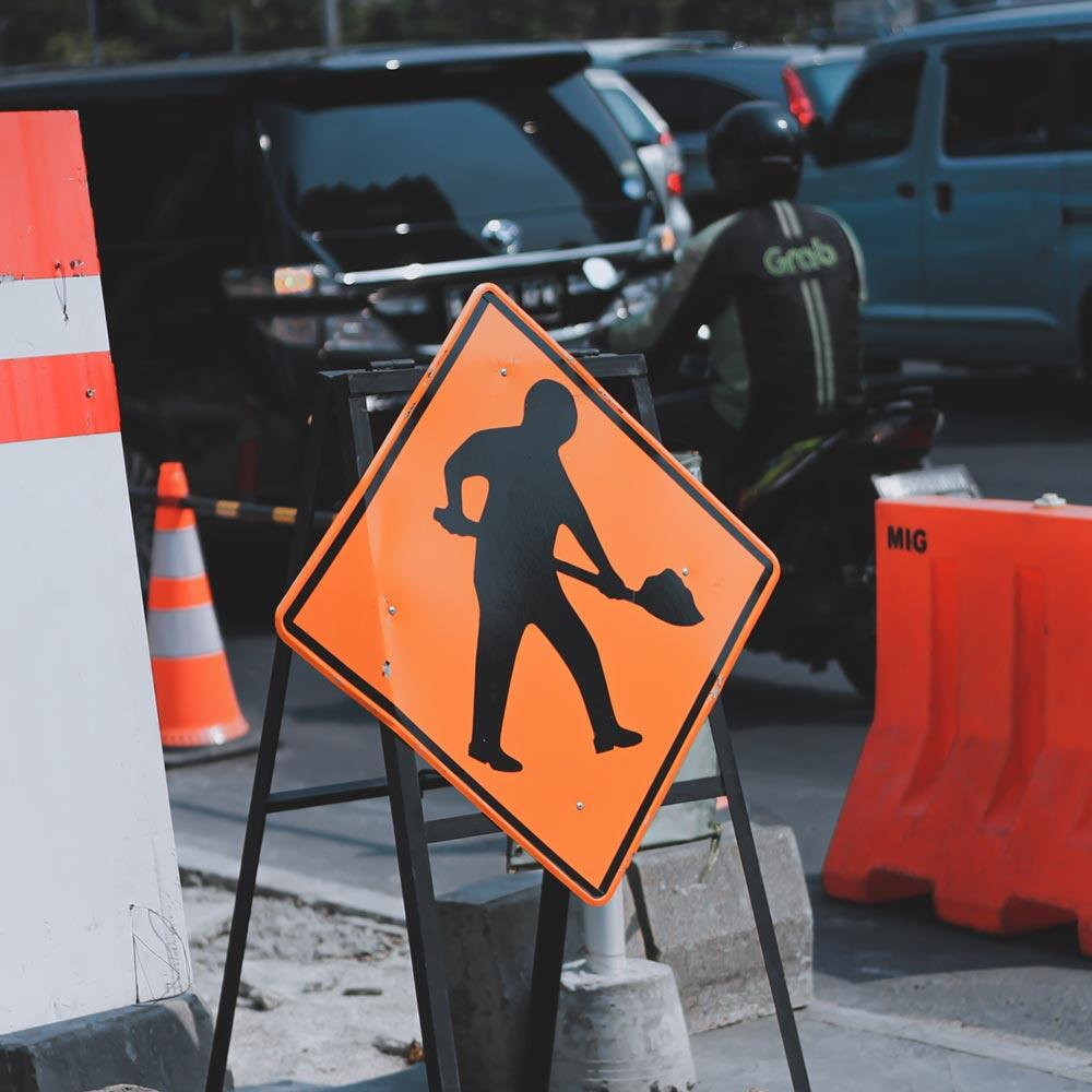 A road work ahead sign on the edge of a construction buffer zone