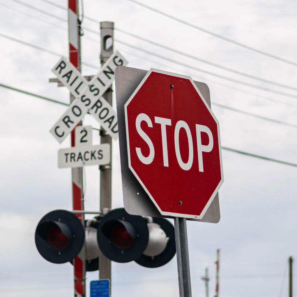 A railroad crossing and stop sign, two signs that have two specific road sign shapes and colors