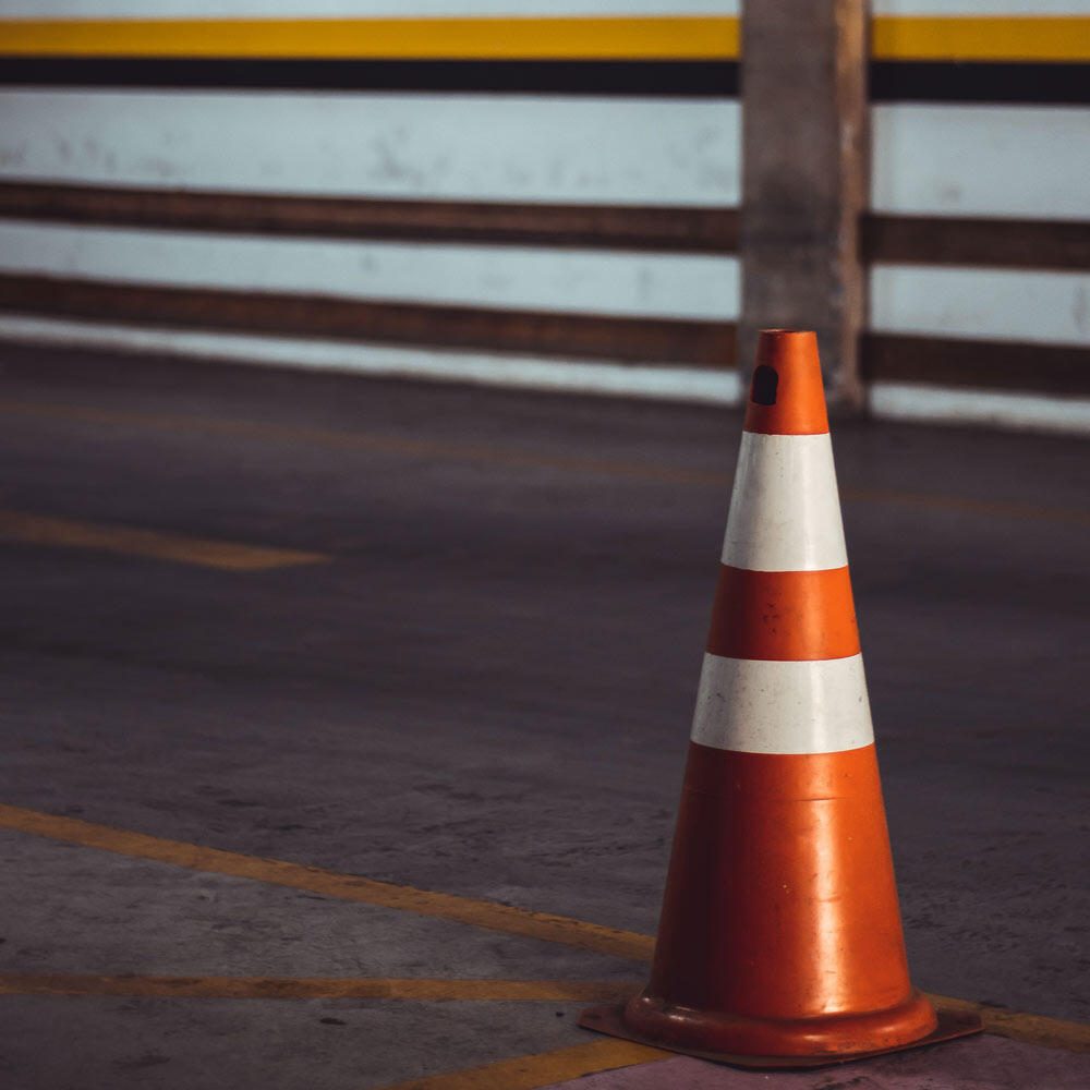 An orange cone with two reflective collars in a parking garage being used as a piece of traffic safety equipment
